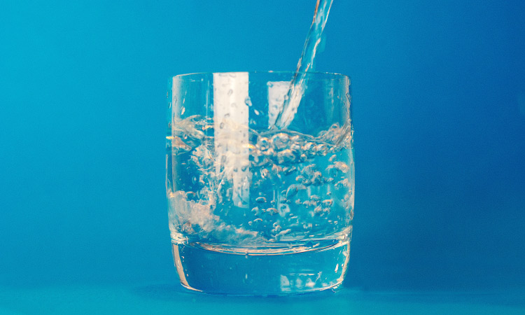 A stream of water being poured into a small glass against a blue background