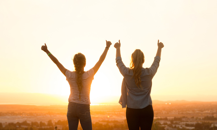 Back view of 2 young women overlooking a valley holding their arms up giving a thumbs-up as the sun sets