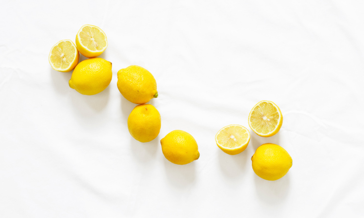 Aerial view of a cluster of yellow lemons, a few cut in half, against a white marble counter