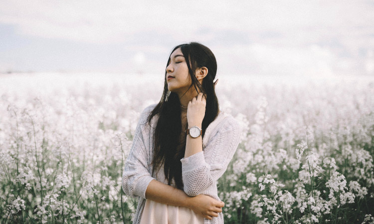 Dark-haired woman in a field of white flowers breathes in deeply as she tries to calm her dental anxiety